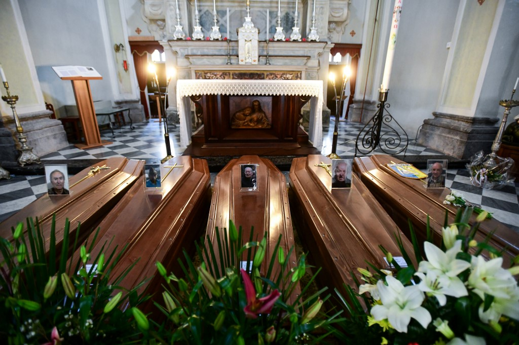 This picture taken on March 21, 2020 shows coffins on the ground of the church in Serina, near Bergamo, northern Italy. - Italy on March 21 reported 793 new coronavirus deaths, a one-day record that saw the country's toll shoot up to 4,825, the 38.3 percent of the world's totality. The total number of fatalities in the northern Lombardy regions around Milan are more than 3,000. (Photo by Piero Cruciatti / AFP)
