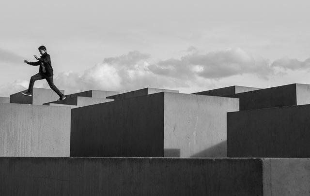 Ein Junge springt über Betonstelen